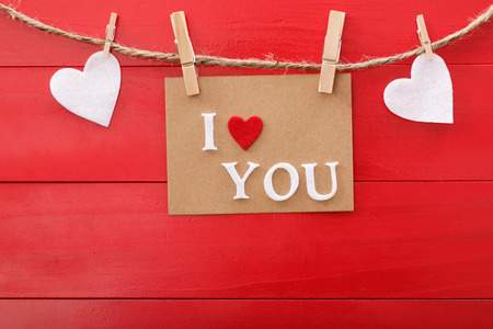 I Love You message card and felt hearts with clothespins over red wooden board photo