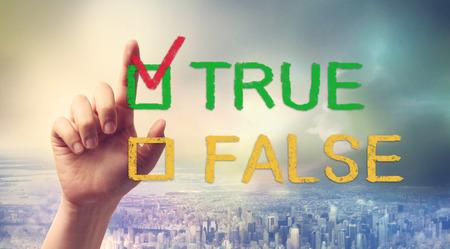 falso: Mano que señala en casilla VERDADERO o FALSO Foto de archivo