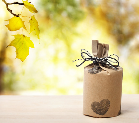 birthday gift: Present wrapped in a rustic earthy style over yellow forest Stock Photo
