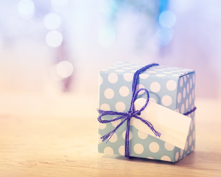 blue box: Polka dot present box with label in a bright room Stock Photo