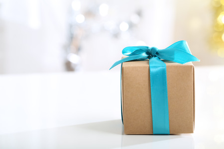 blue gift box: Present box with teal bow in a bright room