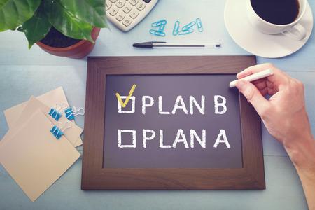 Man controleren PLAN B op een schoolbord