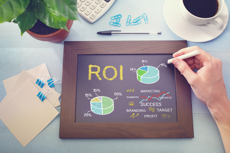 Man drawing ROI concept on chalkboard (return on investment) photo