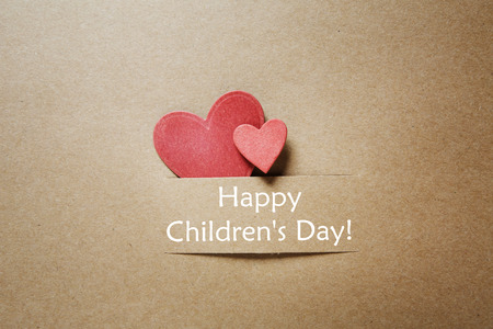 hand crafted: Childrens day message with handmade red paper hearts Stock Photo