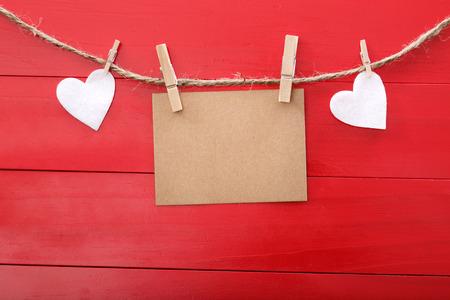 Lege berichtkaart en gevoelde harten met wasknijpers over rode houten raad