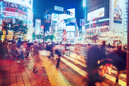 paso de peatones: Las personas y los vehículos cruzan la famosa intersección concurrida de Shibuya en Tokio Foto de archivo