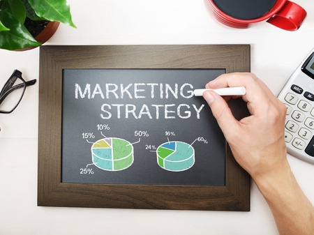small business: Marketing strategy sketched on a little black chalkboard Stock Photo