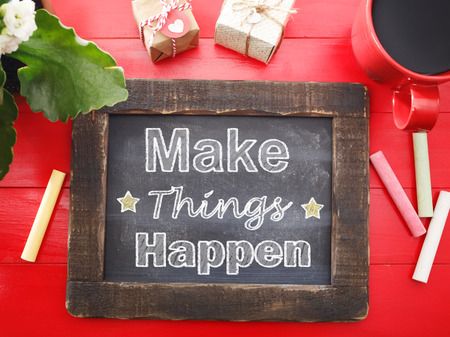 make a gift: Make Things Happen message written on a vintage chalkboard on a red table