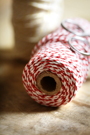 Spool of red and white twine with scissors on wooden background