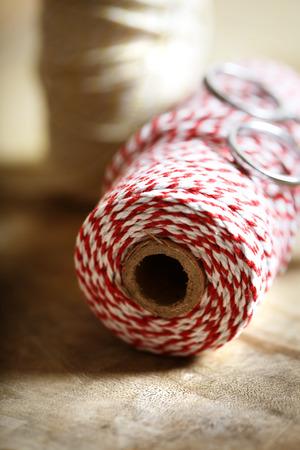 hilo rojo: Carrete de hilo de color rojo y blanco con las tijeras en el fondo de madera
