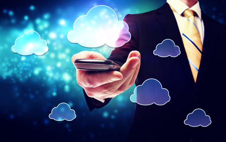 Business man holding a mobile phone with cloud connection concept