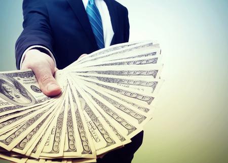 ビンテージ ライトで現金の普及を表示するビジネスの男性 写真素材