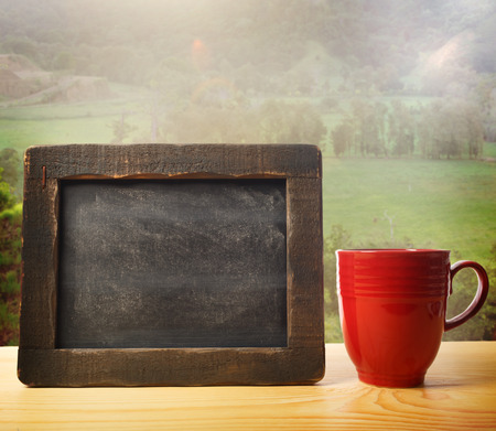 Blank rustic chalkboard with red mug over country landscape Фото со стока