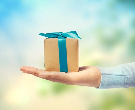 손에 작은 블루 리본 선물 상자