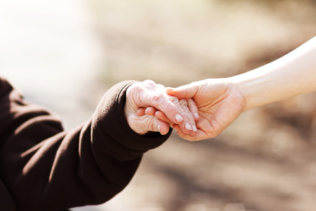 two wheel: Elderly woman holding hands with young caretaker