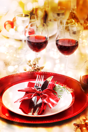 Red and gold themed holiday dinner table setting photo