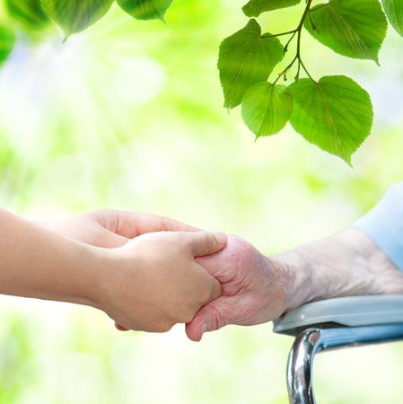 Elderly woman in wheel chair holding hands with young caretaker