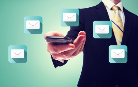 Businessman holding a cell phone with email icons Banco de Imagens - 31016273