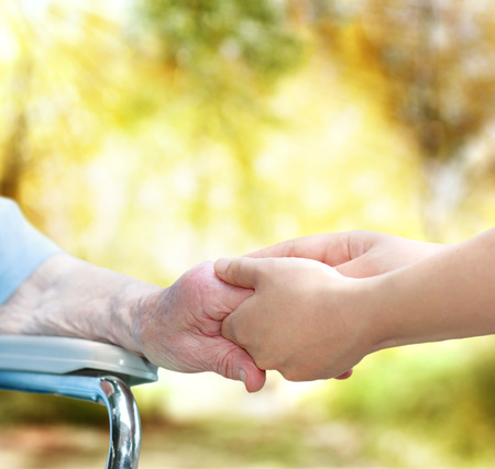 seniors care: Elderly woman in wheel chair holding hands with young caretaker in autumn Stock Photo