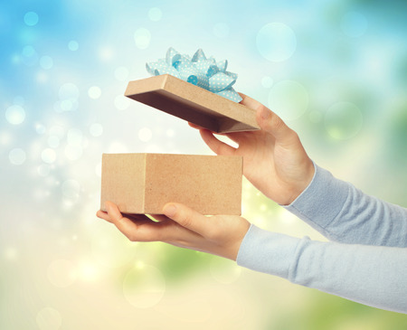 Woman opening and presenting gift box on bright background