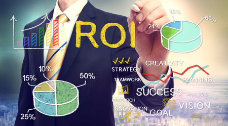 Businessman drawing ROI (return on investment) with graphs Archivio Fotografico