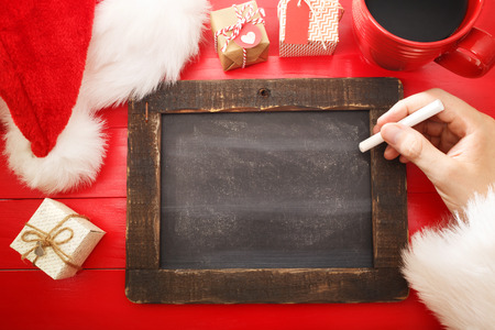 small table: Small blank blackboard with Christmas wishlist on red table