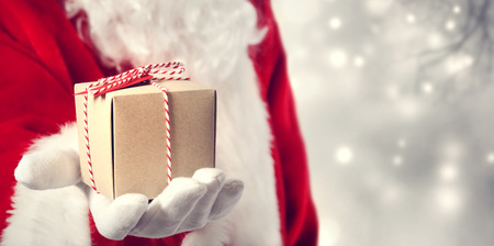 giving gift: Santa Claus holding a gift in his hand  Stock Photo