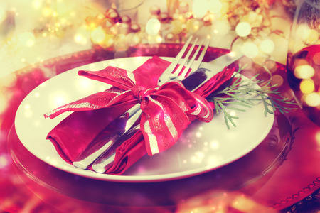 Red and gold themed holiday dinner table plate setting photo
