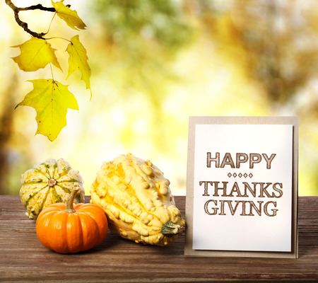 Happy Thanksgiving message card with pumpkins over yellow leaves photo