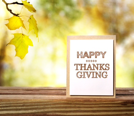 Happy Thanksgiving message card over fall leaves background