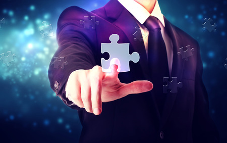 Piece of puzzle with businessman over blue tech background