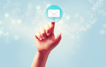 email us: Hand pressing a envelope icon over light blue background Stock Photo