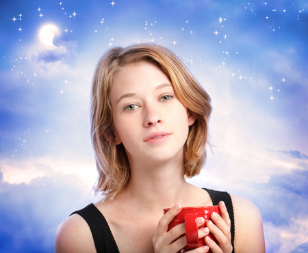 Young woman enjoying a cup of coffee at night Stock Photo