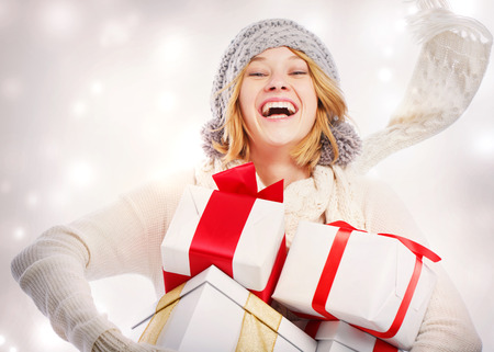 Happy young woman carrying Christmas presents