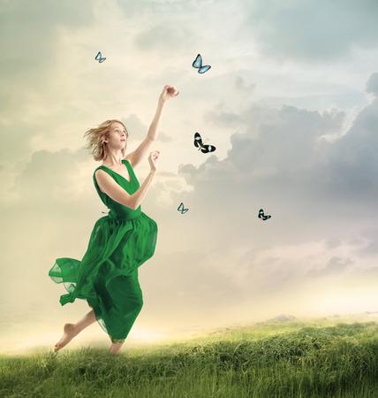 Krásná dívka v zelených šatech po motýly na hory