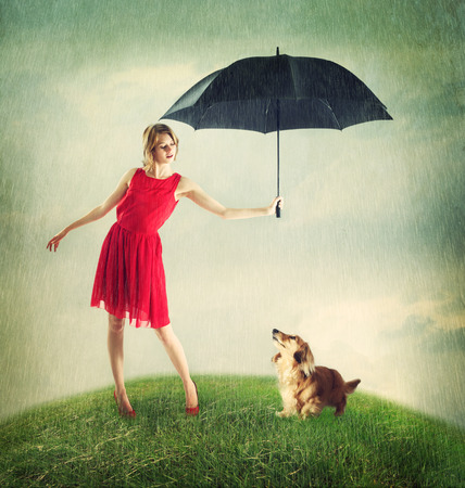 girl in rain: Young Woman in Red Dress Shielding Her Dachshund Dog from the Weather