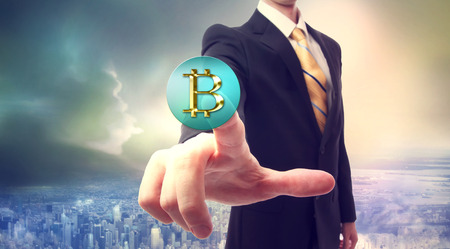 bit: Businessman pressing a Bitcoin button over big city background Stock Photo