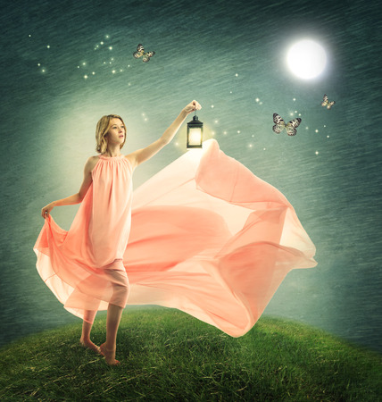 Young woman on a fantasy grassy hilltop with antique lamp photo