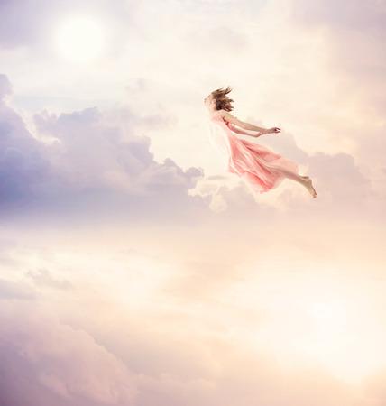 Meisje in een roze jurk vliegen in de lucht. Sereniteit.
