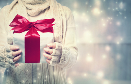 gifts: Woman holding a giftbox with red ribbon in the snowy night Stock Photo
