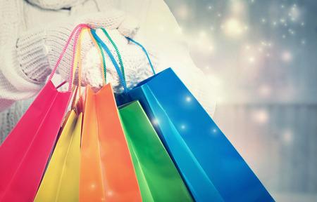 雪夜のカラフルなショッピング バッグを持った女性 写真素材