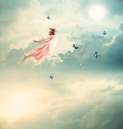 Blonde Girl Flying with Butterflies at Twilight Stockfoto