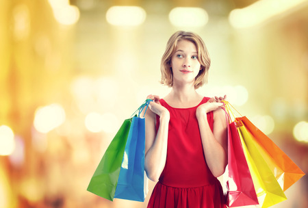 sale shop: Young woman in a red dress with colorful shopping bags Stock Photo