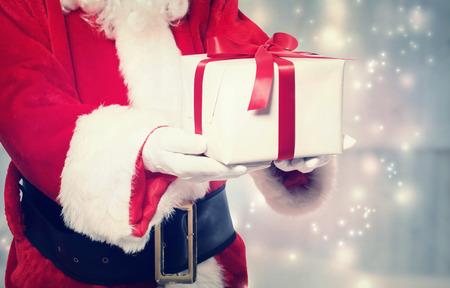 Papá Noel que da un regalo de Navidad con la cinta roja Foto de archivo