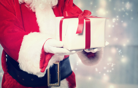 to santa: Santa Claus giving a Christmas present with red ribbon