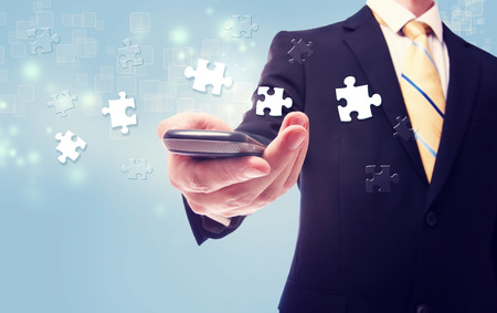 cellphone: Businessman with puzzle over cellphone on light blue background