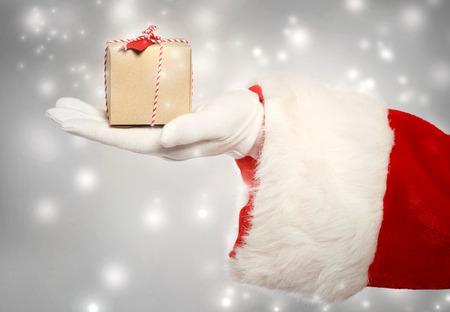 santa claus: Pap� Noel que da un peque�o regalo caja de navidad en noche de nieve Foto de archivo