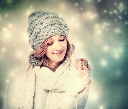 dar un regalo: Mujer joven feliz celebración de una pequeña caja de regalo