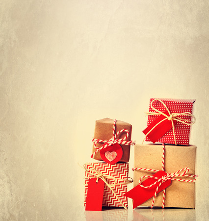 Small red handmade gift boxes on pastel background photo