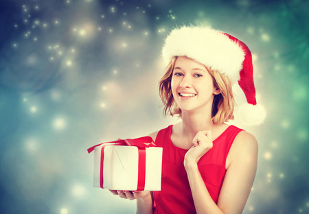 Happy young woman with Santa hat holding a gift box photo